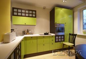 Зеленая глянцевая поверхность кухонной мебели ярко выделяется на фоне белых стен и потолка