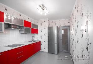 Сдержанный светлый общий фон кухни подчеркивает ярко-красную поверхность кухонной мебели