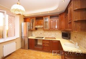 Кухня выполнена из тонированного натурального дерева, что хорошо сочетается с пробковым полом