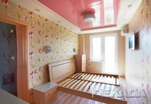 Спальня выдержана в спокойных цветах с акцентом на розовый потолок