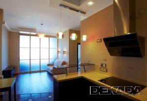 Здесь зона кухни отделена разными видами полов и потолками отличающейся формы